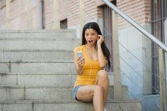 可爱的拉丁妇女shokced看她的电话 库存照片