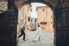 可爱的拥抱的婚礼夫妇在门前站立对老 免版税库存图片