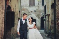 可爱的拥抱的婚礼夫妇在门前站立对老 免版税库存照片