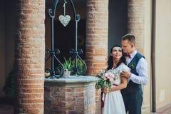 可爱的拥抱的婚礼夫妇在门前站立对老 免版税图库摄影