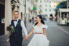 可爱的拥抱的婚礼夫妇在门前站立对老 库存图片