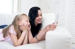 年轻可爱的拿着数字式片剂的妇女和甜矮小的白肤金发的孩子一起填塞观看的互联网 免版税库存图片