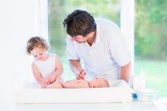 可爱的换尿布的小孩女孩帮助的父亲 免版税库存图片