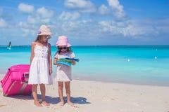 可爱的搜寻在热带海滩的小女孩走的大手提箱和地图方式 图库摄影