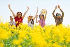 可爱的摆在油菜子领域的妇女和少女 免版税图库摄影