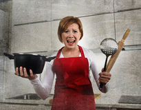 年轻可爱的新人家厨师妇女在举行烹调的红色围裙在家厨房里平底锅和滚针尖叫绝望 免版税库存图片
