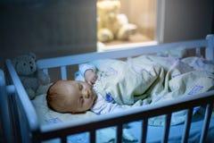 可爱的新出生的男婴,睡觉在小儿床在晚上 免版税图库摄影