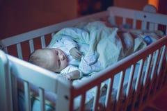 可爱的新出生的男婴,睡觉在小儿床在晚上 免版税库存图片