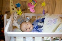 可爱的新出生的男婴,睡觉在小儿床在晚上 免版税库存照片