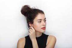 年轻可爱的新鲜的看起来的深色的妇女秀丽画象有接触她的耳朵的高小圆面包发型的 情感和面部expressio 库存图片