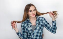 年轻可爱的新鲜的看起来的白肤金发的妇女秀丽画象有头发混乱的在蓝色格子花呢上衣 情感和表情co 免版税图库摄影