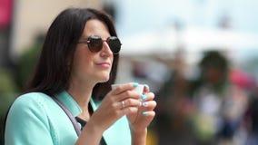 可爱的旅游年轻女人微笑的饮用的咖啡室外享用的都市风景中等特写镜头 影视素材