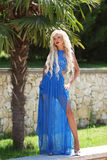 可爱的时尚白肤金发的妇女式样摆在蓝色长的礼服o 免版税库存照片