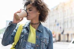 可爱的时髦的女孩享用咖啡户外 免版税库存图片