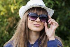 可爱的时髦的时兴的女孩画象太阳镜的和一个帽子以绿色夏天为背景停放 免版税图库摄影