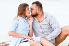 可爱的有吸引力的夫妇一起坐白色沙滩,看,年轻夫妇亲吻在海滩,爱, 库存照片