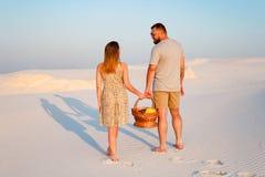 可爱的有吸引力的夫妇在白色沙子海滩或在沙漠或在沙丘、人和一个女孩有一个篮子的在他们的手上 库存图片