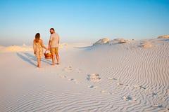 可爱的有吸引力的夫妇在白色沙子海滩或在沙漠或在沙丘、人和一个女孩有一个篮子的在他们的手上 免版税库存图片