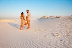 可爱的有吸引力的夫妇在白色沙子海滩或在沙漠或在沙丘、人和一个女孩有一个篮子的在他们的手上 库存照片
