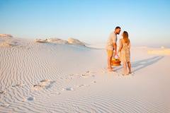 可爱的有吸引力的夫妇在白色沙滩或在沙漠或在沙丘、人和一个女孩有一个篮子的在他们 库存照片