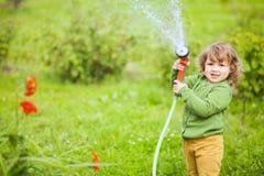 可爱的有小孩小的帮手浇灌庭院和fu 免版税库存图片