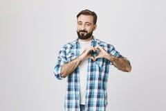 可爱的有胡子的人,微笑恳切地做心脏姿态在胸口附近和身分在灰色背景附近 丈夫展示 免版税库存照片