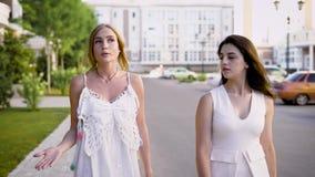 可爱的朋友聊天关于生活在一个夏日,女孩沿街道走并且谈话以轻松的方式 影视素材