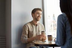 可爱的未剃须的年轻人画象有黑发,微笑的,饮用的咖啡和听的女朋友故事 图库摄影