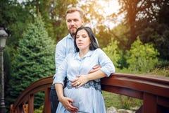 可爱的未来父母年轻微笑的愉快的夫妇浪漫画象在日落期间的在自然苹果树背景 免版税图库摄影
