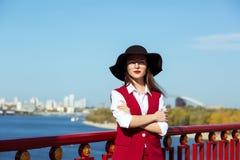 可爱的模型时尚画象穿红色服装的黑帽会议 免版税库存照片