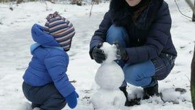 可爱的母亲和婴孩为圣诞节假日雕刻在冬天森林家庭乐趣的小雪人 影视素材