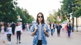 可爱的浅黑肤色的男人定期流逝画象站立在街道由她自己和看照相机的太阳镜的,当 股票视频