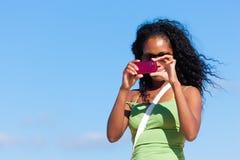 可爱的海滩拍照妇女 免版税库存照片