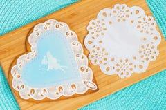 可爱的淡色蓝色姜饼塑造了与逗人喜爱的一点girl& x27的图象的透雕细工心脏; s神仙和网眼图案纸巾 免版税图库摄影