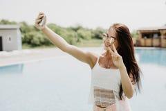 可爱的深色的女孩特写镜头selfie画象有站立近的水池的长的头发的 她穿桃红色T恤杉,太阳镜 她是 免版税库存照片