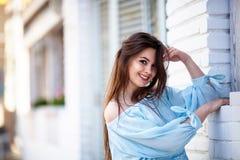 可爱的深色的女孩特写镜头有站立近的咖啡馆的长的头发的 她穿有开放肩膀的蓝色女衬衫 库存照片