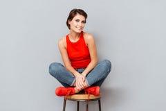 可爱的深色的妇女坐椅子 图库摄影
