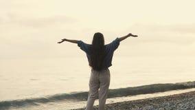 可爱的深色的妇女是上升的手,站立在日落的Pebble海滩 股票录像