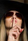 可爱的深色的妇女特写镜头把手指放的比基尼泳装、大帽子和太阳镜的在她的嘴唇上 免版税图库摄影