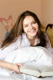 可爱的深色的少妇美丽的愉快的微笑的学生女孩在与看照相机画象的书的床上 免版税库存照片