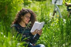 可爱的深色的青少年的读书一本书在一个公园在一个晴天 免版税库存图片