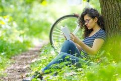 可爱的深色的青少年的读书一本书在公园 免版税库存图片