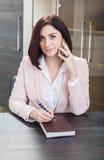 可爱的深色头发的妇女在一米黄衣服idit穿戴了在桌上在有笔记本的一个办公室 免版税库存图片