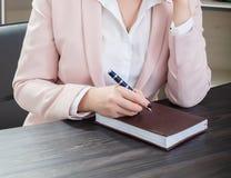 可爱的深色头发的妇女在坐在书桌的一套米黄衣服穿戴了在有笔记本的一个办公室 特写镜头 库存图片