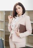 可爱的深色头发的妇女在站立在桌附近在办公室和拿着笔记本的一套米黄衣服穿戴了 免版税库存图片