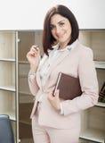 可爱的深色头发的妇女在站立在桌附近在办公室和拿着笔记本的一套米黄衣服穿戴了 免版税图库摄影