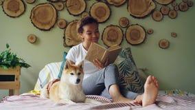 可爱的混合的族种女孩是阅读书和抚摸她的小狗赤足坐在现代公寓的床 爱 股票录像