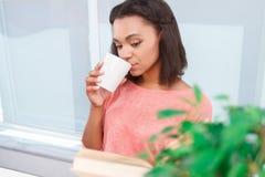 可爱的混血儿夫人饮用的茶和读 库存图片