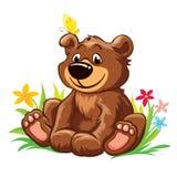 可爱的玩具熊坐草,与在他的耳朵的黄色蝴蝶 免版税图库摄影