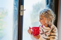 可爱的由窗口的儿童饮用的茶 免版税库存图片
